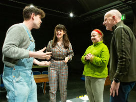 Four actors talking on stage during rehearsals