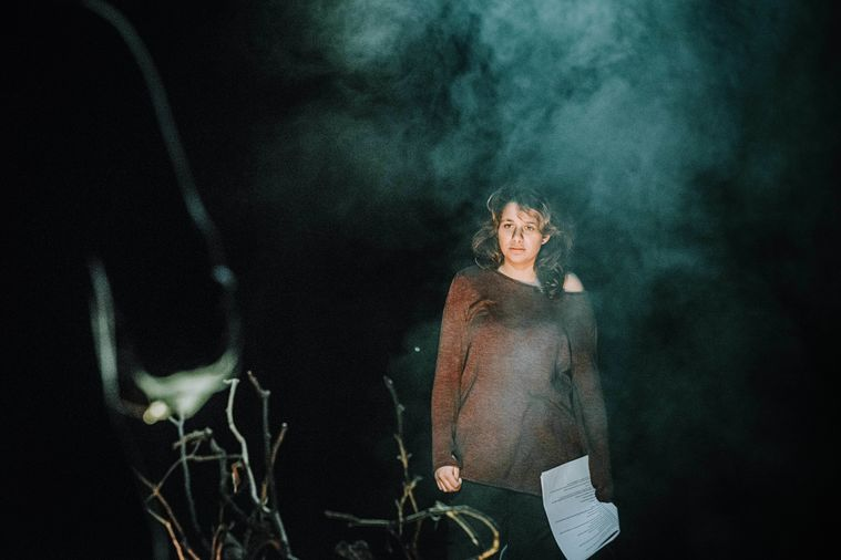 Image shows Safiyya Ingar wearing a brown sweater, holding a script in her left hand, she is looking to her right. The image is smoky, symboling a fire. To the left of the image we can see a hand, out of focus.