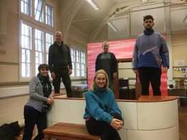 Red Skies cast members are directors pose for a photo on stage in the rehearsal room