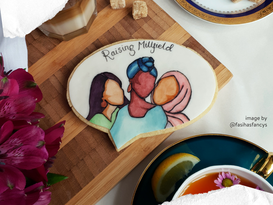 Image shows two logos top left for Peterborough Presents and Eastern Angles. In the centre is an iced biscuit with the words Raising Millfield and a hand drawn image of 3 women, one wears a headscarf another wears a hijab. The biscuit is surrounded be cups of tea and a bunch of pink flowers is to the left.